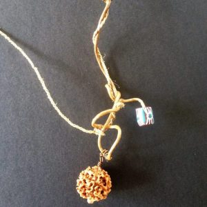 A dainty and organic necklace created from banana fiber and blue Quondong seeds.
