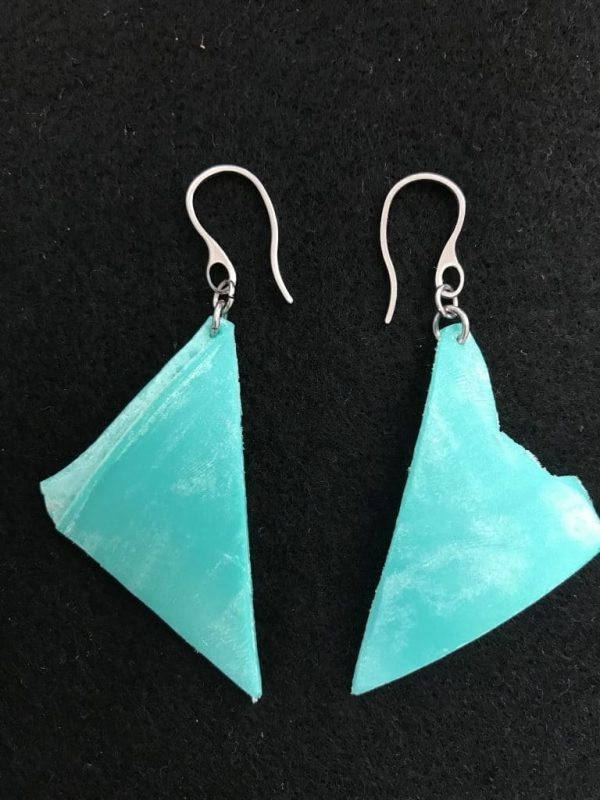 A pair of triangular earrings handmade from aqua coloured marine plastics washed up on the beach